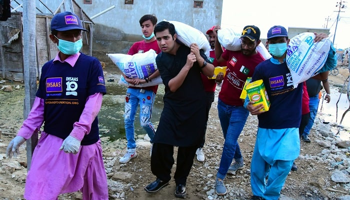Syed Iqrar ul Hassan distributing Rations to flood victims